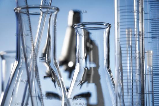Glaskolben, Mensuren und Mikroskop im Labor