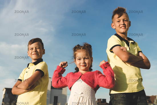 two young brothers in yellow T-shirts and a sister showing muscles in her arms. outdoors in summer. against the sky