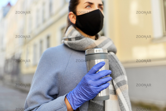 woman in reusable mask with tumbler in city
