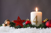 Candle of the fourth Advent burns, fir branches and Christmas tree balls in the snow