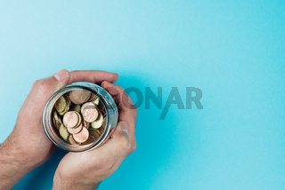 above view of hands holding jar filled with small change