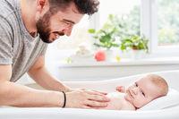 Vater wäscht Baby in Badewanne im Bad