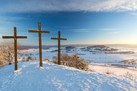 Three summit crosses on a mountain peak in a beautiful winter landscape in the Swabian Alps at sunset
