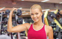 happy young woman with dumbbells exercising in gym