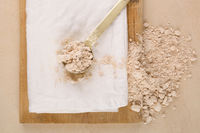 Wholegrain flour and scoop on wooden board.