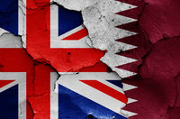 flags of UK and Qatar painted on cracked wall