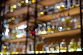 Defocused background of bar counter with various bottles of alcohol.