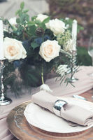 Candles and vase with white roses placed on round table near wineglasses