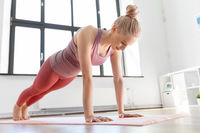 young woman doing plank exercise on mat at home