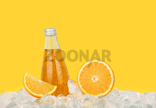 One glass bottle of orange drink on ice