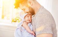Vater beim Abtrocknen von Baby mit Handtuch