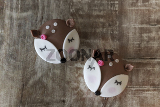 Cute deer cupcakes on wooden table
