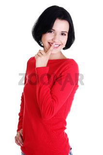 Happy woman making a keep it quiet gesture