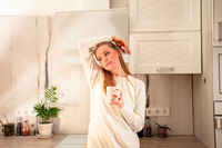 Nice woman drinking morning routine coffe in the kitchen
