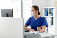 doctor or nurse in mask with clipboard at hospital
