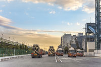 Sunset on concrete mixing transport trucks parked in the Odaiba Bay industrial harbor in