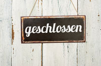 Old metal sign in front of a white wooden wall - german word for closed - geschlossen
