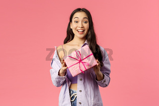 Got present for you. Excited happy young asian girl holding wrapped box with gift, congratulating with holiday or birthday, being invited b-day party, standing amused pink background