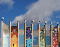 the brightly coloured facade of the new west yorkshire playhouse theatre building against a bright cloudy blue sky