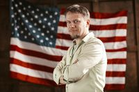 Patriotic American Businessman Amid On American Flag Blurred Back