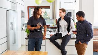 Männer als Freunde unterhalten sich beim Wein trinken auf Feier in Küche