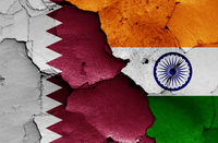 flags of Qatar and India painted on cracked wall