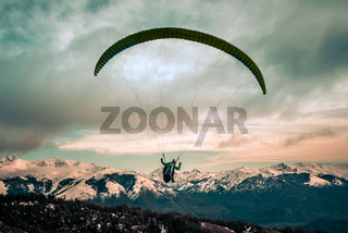 Rear view of paragliding over mountains of Bariloche in Argentina, with snowed peaks in the background. Concept of freedom, adventure, flying