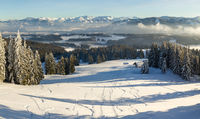 Amazing Panorama View from Snow Mountain with Forest to snowy and foggy Mountain Range. Mountain Hut Klings Huette on Hauchenberg near Diepolz in Allgau, Bavaria, Germany.