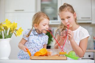 Kinder trinken frisch gepressten Orangensaft