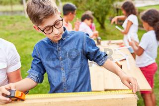 Kind beim Holz messen mit dem Zollstock