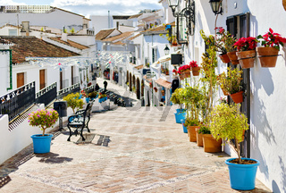 Idyllic scene picturesque street small white-washed village of Mijas. Path way decorated with hanging on houses walls plants in bright flowerpots, famous place Costa del Sol, Andalusia, Málaga, Spain
