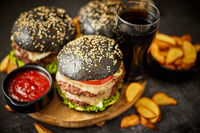 Homemade delicious black burgers served on wooden cutting board with ketchup, potato wedges