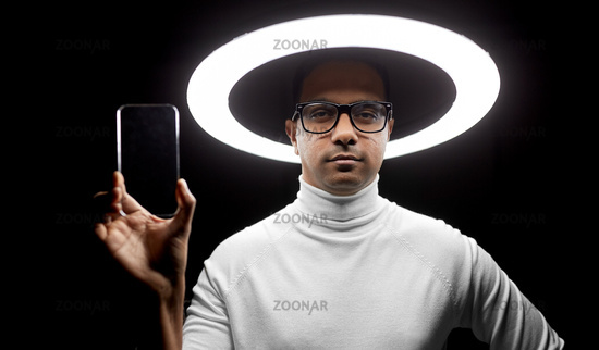 man in glasses with smartphone under illumination