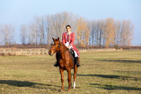 Hungarian csikos horsewoman in traditional folk costume