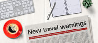 Newspaper on a desk -  New travel warnings