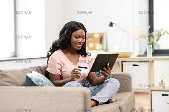 happy woman with tablet pc and credit card at home