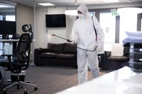 Health worker wearing protective clothes cleaning the office using disinfectant