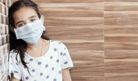 Concept of PTSD or post-traumatic stress disorder after covid-19 or coronavirus pandemic - Young teenager girl with medical mask wearing sat by leaning on well in sad, fear, or anxiety.