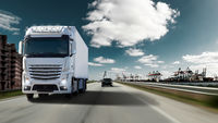 Fast moving truck with full lighting on a motorway with port for container ships. Water, cranes and warehouses with an imposing sky.