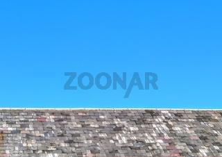 Grey slate roof against deep blue sky background