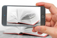 Book on smartphone screen. Big open book. Pages of new book. Training and Education on pages of books.