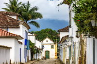 Street with its lanterns, colonial style houses, cobblestone pavement and historic church in the background