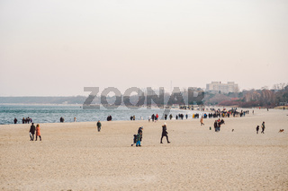 People walk on sandy beach in winter. Perfect winter vacation. People chill out in cold season on coast. Gdansk, Poland February 9, 2020. Walking crowd of people in city Sopot along beach Baltic Sea