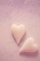 Two glass hearts on stone background in vintage pastel colors - soft focus. Symbol of love. Space for text.