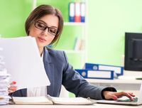 Young female employee very busy with ongoing paperwork