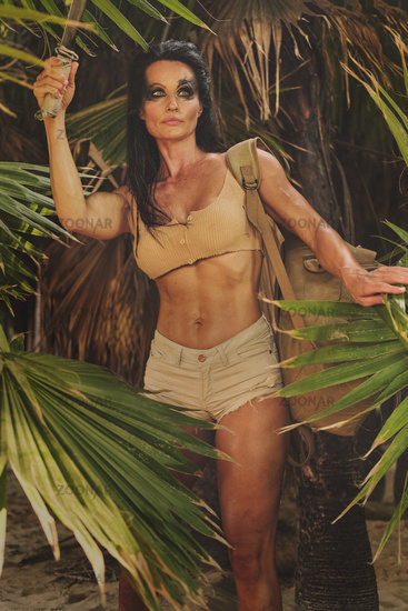 Athletic woman holding machete posing in palm trees forest