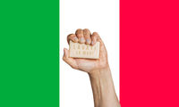 Caucasian male hand holding soap with words: Lavati le mani, in Italian against an Italian flag background