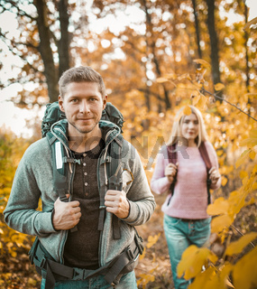 Couple Of Backpackers Walking Through Autumn Forest