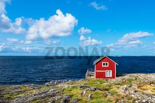 Rote Holzhütte auf der Insel Åstol in Schweden