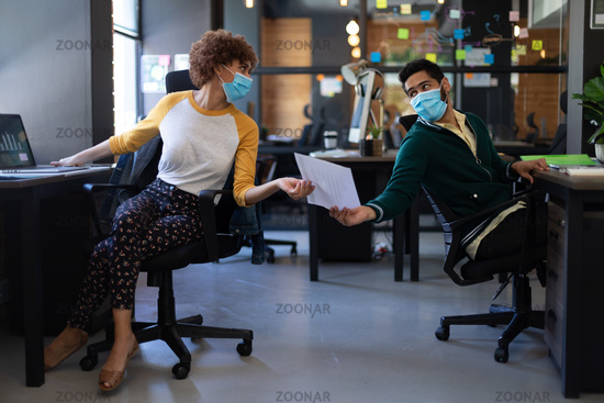 Mixed race woman and man wearing face masks passing document in casual office